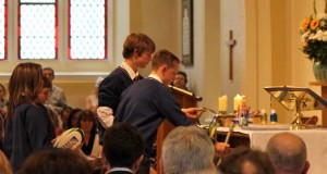 Students bring items representing school life to the altar during the service of dedication of Temple Carrig School